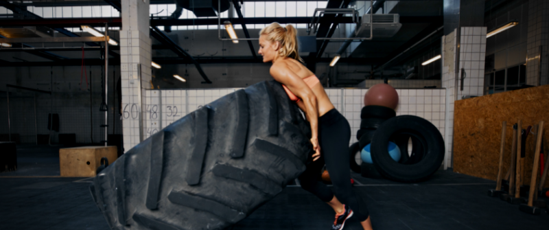 crossfit_woman flipping tire in crossfit gym
